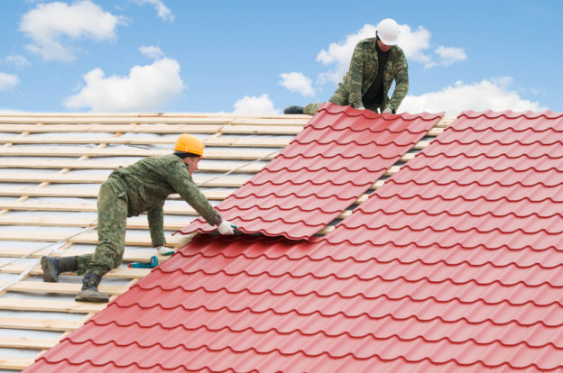 roof replacement tiles being placed by two roofers